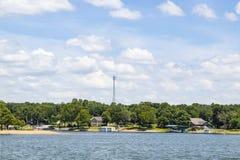 Brzeg jeziora stwarza ognisko domowe i łódź doki z drzewami i nadajnikiem górują w tle pod niebieskim niebem z puszystymi chmuram obraz stock