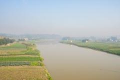 Brzeg rzeki kultywował ziemię uprawną w pogodnym mgłowym zima ranku Fotografia Stock