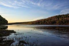 Brzeg rzeki w położenia słońcu, spokoju przepływie i ciszy, zdjęcia royalty free