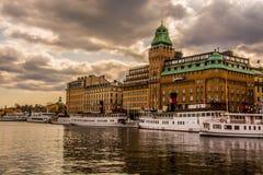Brzeg rzeki w Sztokholm z dramatycznymi chmurami i hotelem Fotografia Royalty Free