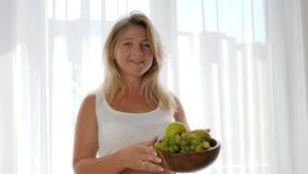 Brzemienność, kobieta z dużym brzuszkiem je winogrona blisko okno i trzyma drewnianego talerza zbiory