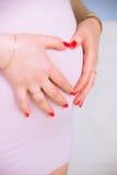 Brzemienność, narodziny, ciężarny, brzuch, trzeci trymestr, menchia, gwoździe, czerwień, manicure, nowy życie, Fotografia Stock