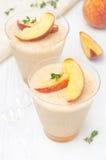 Brzoskwini i jabłka souffle w porcyjnych szkłach Zdjęcia Stock