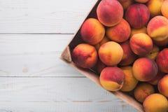 Brzoskwini owoc na drewnianym koszu Fotografia Royalty Free