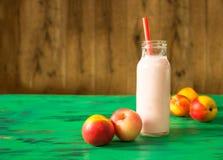 Brzoskwini owocowy smoothie w szklanej butelce na zielonym drewnianym stole Zdjęcie Stock