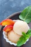 Brzoskwinia lody i brzoskwini plasterki w białym pucharze Obraz Stock