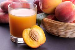 Brzoskwinia sok w szkle obok świeżego brzoskwini zbliżenia na ciemnym tle obraz stock