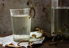 Brzozy detox naturalny sok w szkle na brzozy barkentynie z brzozy gałąź i ornamentu geometryczne tła księgi stary rocznik rusty m Fotografia Royalty Free