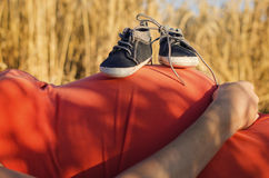 Brzuszek kobieta w ciąży z dziecka butami Fotografia Stock