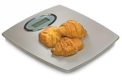 Báscula de baño de Digitaces y Croissants, aislados Foto de archivo libre de regalías