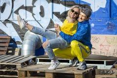 BSports grabb med en flicka på gatalekplatsen Grafittiskridskolekplats royaltyfri fotografi