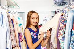 Búsqueda feliz para la ropa en suspensiones en tienda Foto de archivo libre de regalías