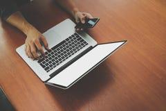 Bästa sikt av affärsmanhanden genom att använda på den smarta telefonen och bärbara datorn Arkivfoton