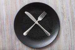 Bästa sikt av den svarta plattan med bestick på grå färger Royaltyfri Foto
