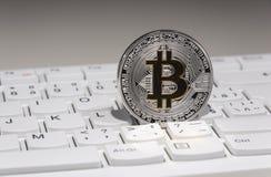 BTC Bitcoin coin on keyboard Stock Photo