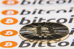 BTC Bitcoin coin. Shining metal BTC bitcoin coin on background from repeating bitcoin writings Royalty Free Stock Image