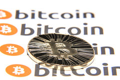BTC Bitcoin coin. Shining metal BTC bitcoin coin on background from repeating bitcoin writings Stock Images