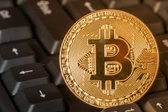 BTC coin on computer keyboard. One golden BTC coin on computer keyboard Royalty Free Stock Photography