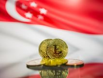 Bitcoin gold coin and defocused flag of Singapore background. Virtual cryptocurrency concept. royalty free stock photos