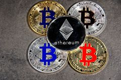 BTC ETH Bitcoin Ethereum coins. Shining gold and silver metal BTC ETH Bitcoin Ethereum coins on grey background Royalty Free Stock Photography