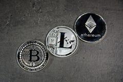 BTC LTC ETH Bitcoin Litecoin Ethereum coins. Shining silver metal BTC LTC ETH Bitcoin Litecoin Ethereum coins on grey background Royalty Free Stock Photos