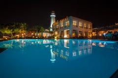 Bâtiment d'hôtel de nuit derrière la piscine Photographie stock libre de droits