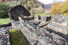 Bâtiments ruinés de mine d'avance avec le barrage dans la distance Image stock
