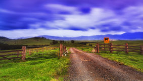 BTops gloucester Rd Gate Cattle sign. Agricultural rural farm land with green pastures behind cattle gate with grid at sunset in Cobark Barrington tops of Stock Photo