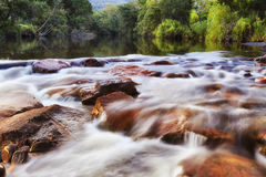 BTops Gloucester Riv Riffle. Stone riffles on rapid mountain Gloucester river below still waters with reflecting green trees Royalty Free Stock Image