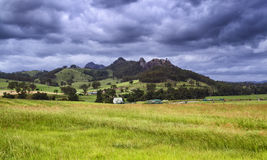 BTops Gloucester Rocks Field. Green cultivated agricultural field against distant rocky mountain under stormy cloud sky in picturesque country of regional NSW Stock Image