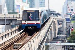 BTS Skytrain überschreitet vorbei auf erhöhte Schienen über Sukhumvit-Straße in Bangkok, Thailand Lizenzfreie Stockfotos