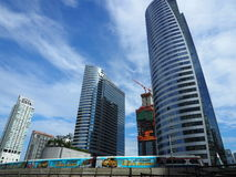 A BTS Skytrain passes in front of modern office buildings Stock Images