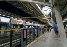 Skytrain railway station showing double sided clock and a long platform with arrows sign in-out direction to the carriage. BTS skytrain railway station showing royalty free stock photography