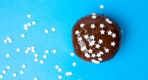Buñuelo adornado del chocolate en fondo azul Fotos de archivo libres de regalías