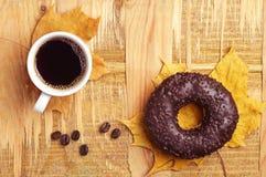 Buñuelo, café y hojas de otoño Imagen de archivo libre de regalías
