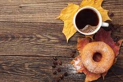 Buñuelo, café y hojas de otoño Fotos de archivo libres de regalías