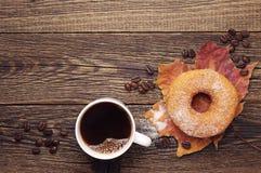 Buñuelo, café y hojas de otoño dulces Foto de archivo