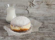 Buñuelo con el azúcar en polvo y la taza de leche Fotografía de archivo