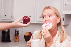 Buñuelo contra la decisión sana de la consumición de la fruta Fotos de archivo