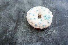 Buñuelo de la Navidad con los copos de nieve azucarados comestibles en fondo oscuro Alimento delicioso Endecha plana, visión supe Fotos de archivo libres de regalías