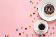 Buñuelo del chocolate con una taza de café en un fondo rosado espacio Foto de archivo libre de regalías