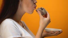 Buñuelo del chocolate de la muchacha que muerde, comida dulce alta en calorías, diabetes creciente de la glucosa almacen de video