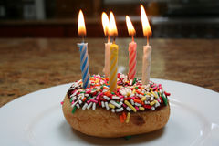 Buñuelo del feliz cumpleaños con las velas rayadas Fotografía de archivo