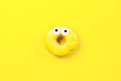Buñuelo redondo con los ojos en fondo amarillo Endecha plana, visión superior Imagenes de archivo
