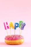 Buñuelo rosado con las letras felices Fotos de archivo