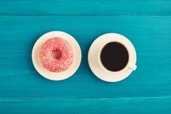 Buñuelo rosado con una taza de café en una tabla de madera Imagen de archivo libre de regalías