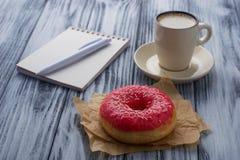 Buñuelo, taza de café y cuaderno Fotografía de archivo