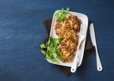 Buñuelos de la coliflor y del pollo en un fondo azul, visión superior Aperitivo delicioso fotos de archivo