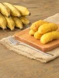 Buñuelos del plátano en la tajadera de madera Imagen de archivo