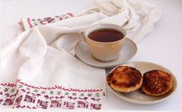 Buñuelos del requesón de la taza de té y una toalla Fotografía de archivo libre de regalías